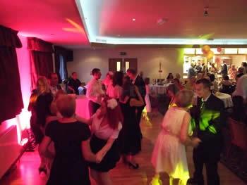 Wedding guests dancing at Blackley Golf Club with red venue lighting