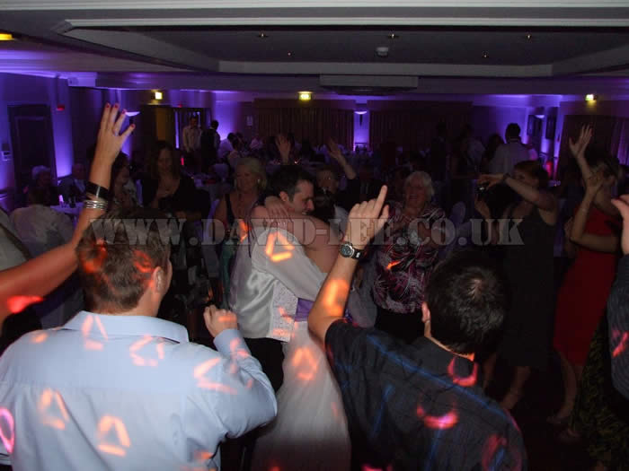 Bride and groom dancing the finale with everyone joining in at village hotel in cheadle
