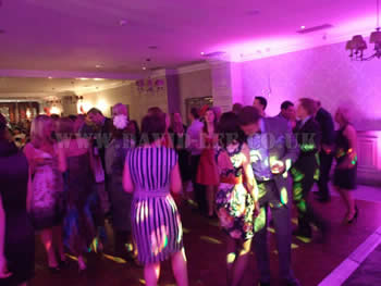 Wedding guests dancing at Mottram hall with pink lighting