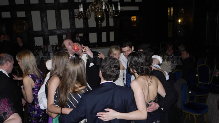 Bramall hall wedding guests enjoying a group hug and sing a long